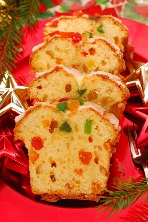 traditionele kerst cake (keks) met gedroogde vruchten, gelei en kers op rode plaat