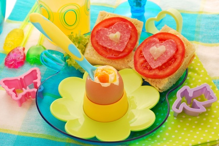 breakfast with soft boiled egg,juice  and sandwiches for child photo