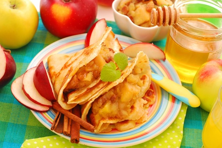 pancakes stuffed with stewed apples , raisins ,honey and cinnamon as dessert for baby Stock Photo