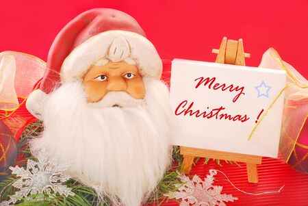 christmas decoration with head of santa claus figurine and  wooden easel for wishes photo