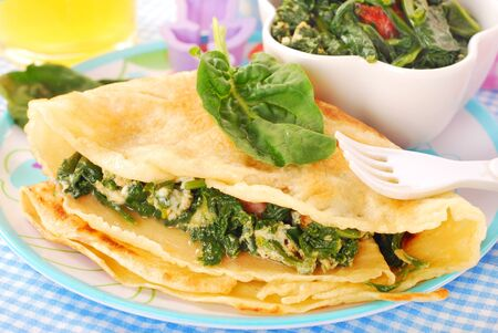 crepe: plate of pancake stuffed with spinach ,bacon and eggs for child