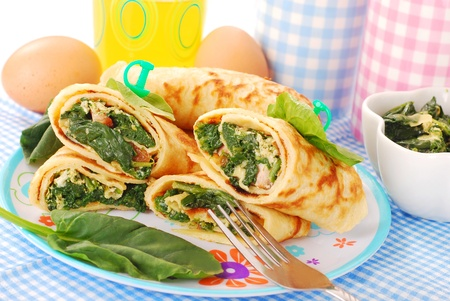 crepe: plate of rolled  pancakes stuffed with spinach ,bacon and eggs