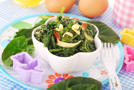 baby spinach: bowl of boiled spinach with egg and cheese for baby Stock Photo