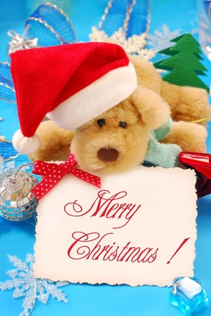 sweet puppy mascot in santa hat  holding banner with christmas greetings  photo