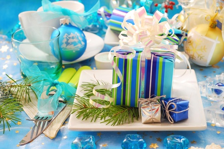 christmas table decoration with gift box on the plate in blue and white color photo