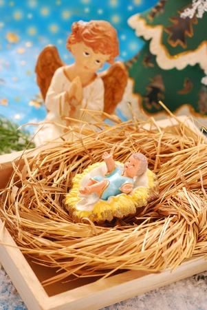 christ is born: nativity scene with baby jesus figurine laying on hay and praying angel