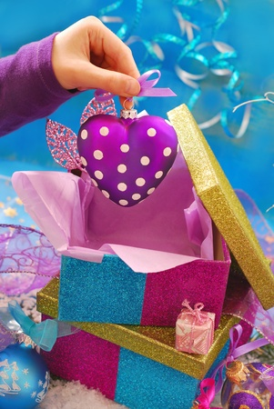 child hand taking purple heart shape christmas bauble out of gift box  photo