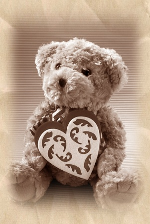 vintage style teddy bear holding a heart ( in sepia ) photo