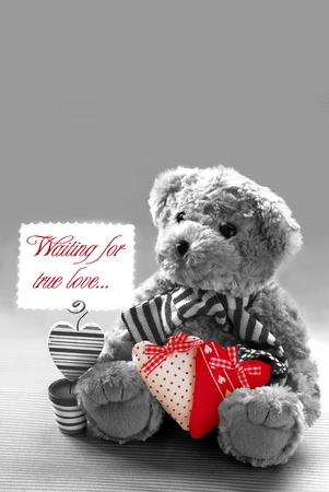 sad love: sad teddy bear holding hearts and card  Stock Photo