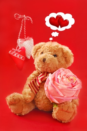 teddy bear sitting with big pink rose and thinking about valentine`s love Stock Photo - 11872482