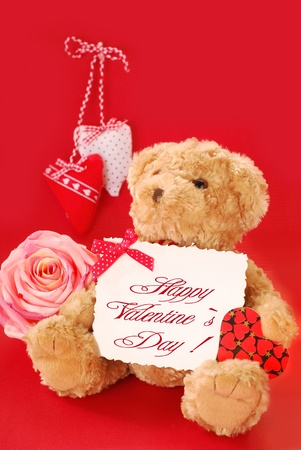 teddy bear holding a card with valentine`s greetings against red background  photo