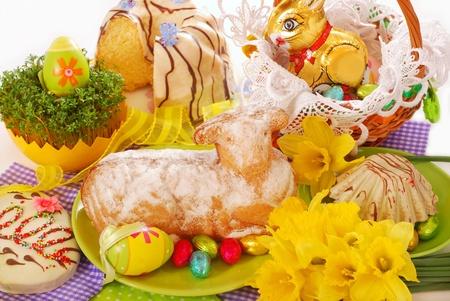 Pasen taart in de vorm van lam en zoetwaren op feestelijke tafel