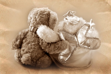 vintage teddy bear`s couple sitting with backand embracing  in sepia photo