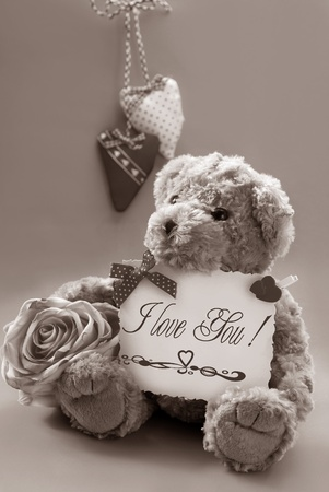 vintage teddy bear holding a card with valentine`s greetings in sepia Stock Photo - 11872488