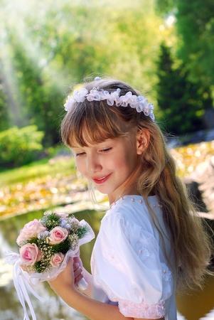 comunion: retrato de una niña de vestido blanco y una corona, de ir a la primera comunión y posando en el parque Foto de archivo