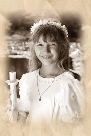 vintage portrait of a girl in white dress and wreath ,going to the first holy communion and posing in the park with candle photo