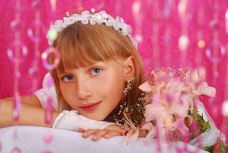 portrait of a girl in white dress and wreath ,going to the first holy communion and posing in studio against pink background photo