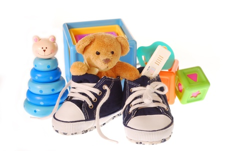 baby boy`s shoes with pregnancy ,teddy bear and toys isolated on white photo
