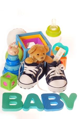 baby boy `s schoenen met zwangerschap, teddy beer, speelgoed, levensmiddelen en letters b, a, b, y op wit wordt geïsoleerd