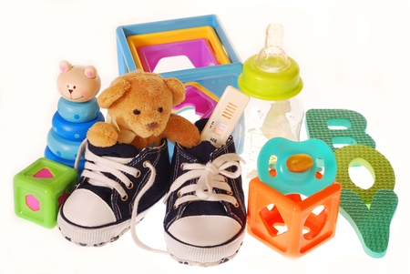 niño bebé `s zapatos con el embarazo, el osito de peluche y juguetes aislados en blanco Foto de archivo