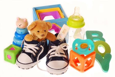 prueba de embarazo: niño bebé `s zapatos con el embarazo, el osito de peluche y juguetes aislados en blanco Foto de archivo