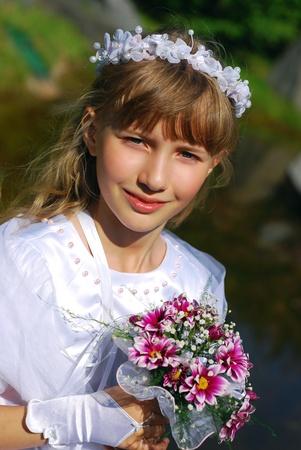 confirmacion: retrato de una niña de vestido blanco y una corona, de ir a la primera comunión y posando en el parque Foto de archivo