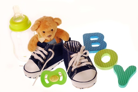 baby boy`s shoes with teddy bear ,stuffs and letters b,o,y isolated on white Stock Photo - 12427750