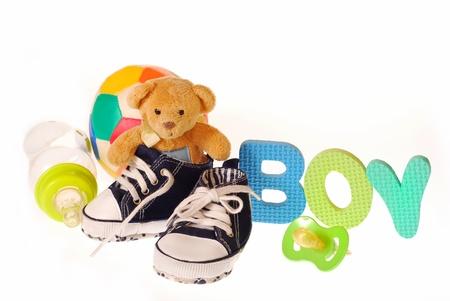 baby boy `s schoenen met teddybeer, levensmiddelen en brieven b, o, y geïsoleerd op wit Stockfoto