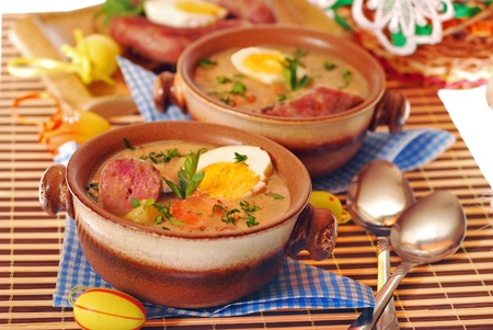stoneware: white borscht with egg and grilled sausage in stoneware bowls for easter dinner