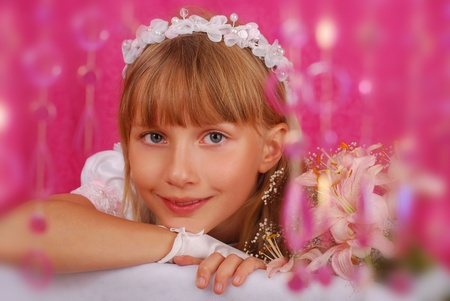 portrait of a girl in white dress and wreath ,going to the first holy communion and posing in studio against pink background Stock Photo - 12827599