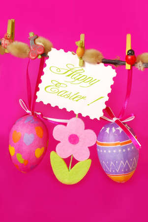 easter decoration with hanging colorful eggs and  felt flowers against pink background photo