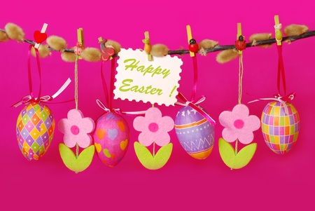 easter border with hanging colorful eggs and  felt flowers against pink background photo