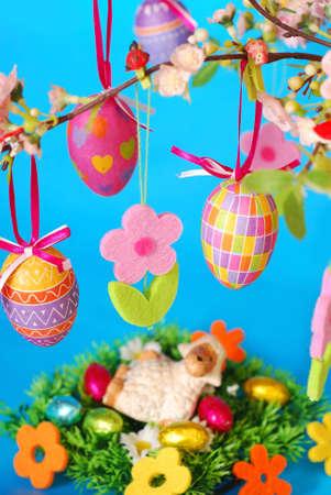 pasen schaap: Pasen decoratie met opknoping kleurrijke eieren, vilten bloemen en lamsvlees beeldje liggend op het gras tegen blauwe achtergrond