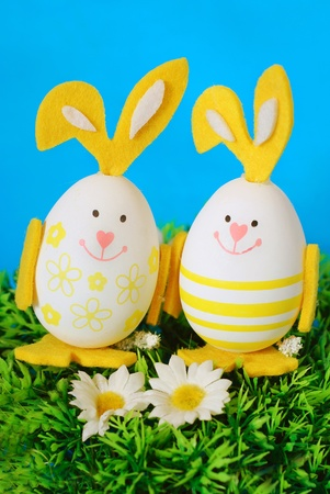 two easter bunny shape eggs standing in grass against blue background  photo