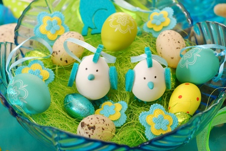 arranging: glass bowl with easter decoration in turquoise-pistachio colors Stock Photo