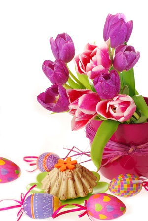 easter decoration with painted eggs,ring cake and bunch of purple tulips in vase isolated on white photo