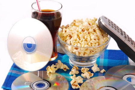 family movies: table with bowl of popcorn,cold drink,dvd discs and remote control