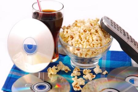 tafel met bak popcorn, koud drankje, DVD-schijven en afstandsbediening