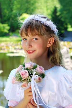 portrait of a girl in white dress and wreath ,going to the first holy communion and posing in park Stock Photo - 13042292