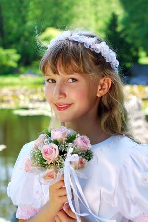 portret van een meisje in witte jurk en de krans, naar de eerste heilige communie en poseren in park