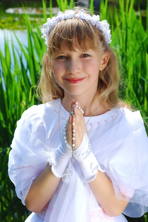 portrait of a girl in white dress and wreath ,going to the first holy communion and posing in park Stock Photo - 13042294