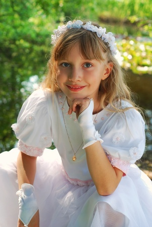 portrait of a girl in white dress and wreath ,going to the first holy communion and posing in park Stock Photo - 13042291