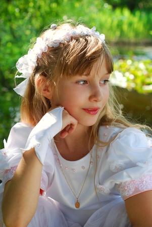 portret van een meisje in witte jurk en kroon, naar de eerste heilige communie en poseren in park