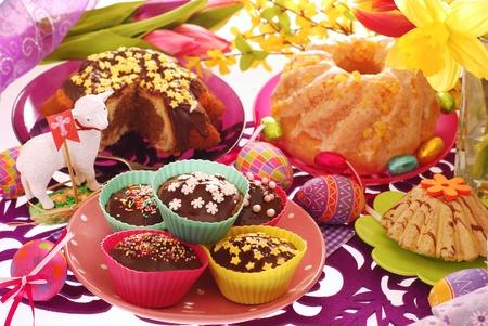 pasen schaap: assortiment van easter zoetwaren (ring cakes, muffins) op kleurrijke feestelijke tafel