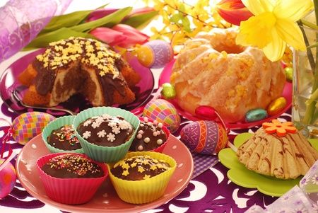 assortment of easter confectionery ( ring cakes,muffins ) on colorful festive table  photo