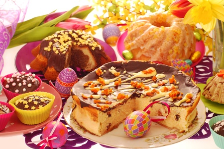assortment of easter confectionery ( cheese cake, ring cakes,muffins ) on colorful festive table  photo