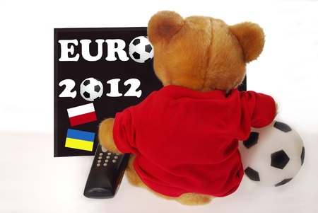 teddy bear sitting back, holding ball and remote control and watching euro 2012 in tv