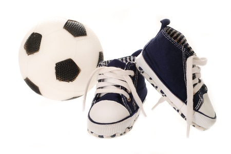 Baby sportschoenen en bal zijn voor de uitrusting van de kleine voetbalfan op wit wordt geïsoleerd Stockfoto