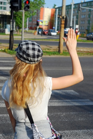 young girl crossing the street alone with hand up photo