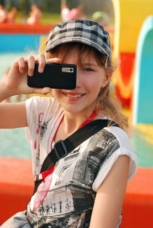 young girl taking photo with mobile phone outdoor photo